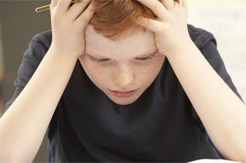Elementary aged boy sitting at desk with head down in his hands